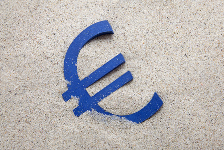Blue euro symbol in the sand Stock Photo