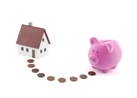 Saving for a house. Piggy bank with coins and house miniature. Stock Photo
