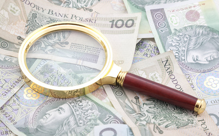 Polish money with golden magnifying glass photo