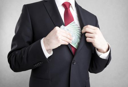 破損。男はスーツの上着のポケットにポーランドのお金を置きます。