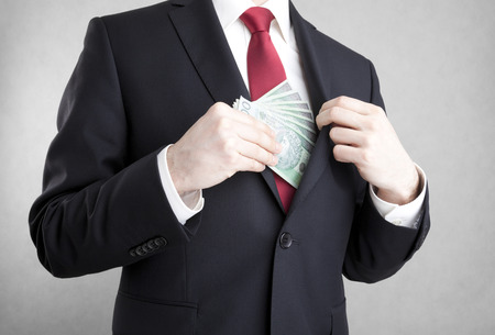 corrupcion: Corrupción. Hombre que pone el dinero polaco en el bolsillo de la chaqueta del traje. Foto de archivo