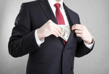 La corrupción en los negocios. Hombre que pone el dinero en el bolsillo de la chaqueta del traje. Foto de archivo