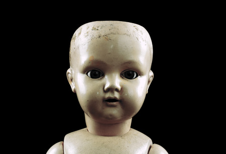 baby doll: Vintage doll face isolated on black  Stock Photo