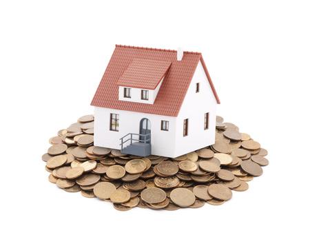 Kleine Spielzeug Haus auf einem Haufen von Münzen Standard-Bild - 41300730