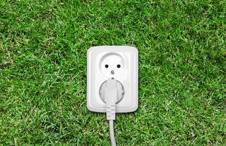 enchufe: Toma de corriente eléctrica en la hierba verde Foto de archivo