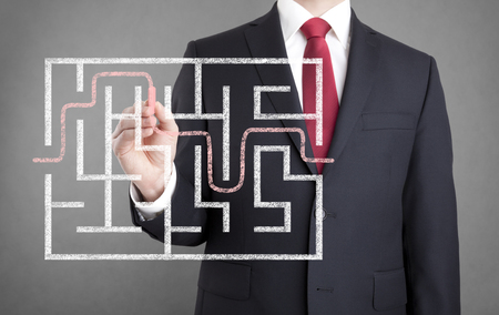 problem solution: Businessman finding the solution of a maze Stock Photo