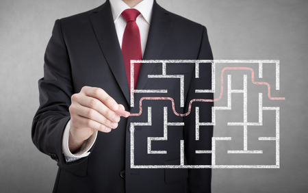 business challenge: Businessman finding the solution of a maze Stock Photo
