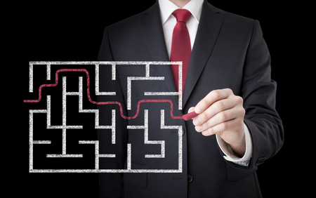 solved maze puzzle: Businessman finding the solution of a maze Stock Photo