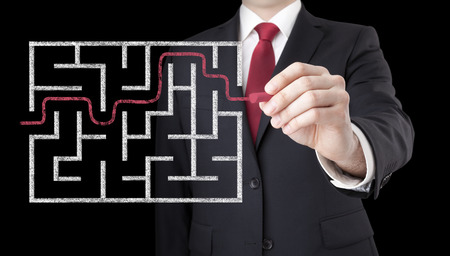 difficult to find: Businessman finding the solution of a maze Stock Photo