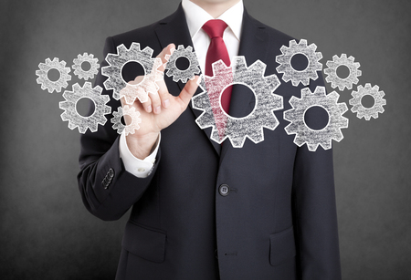 organized: Businessman with gears, concept of well organized work process. Stock Photo