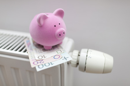 Piggy bank with polish money on radiator. Energy saving concept.
