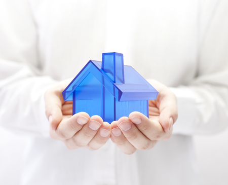 building insurance: Blue house in hands. Home insurance concept. Stock Photo