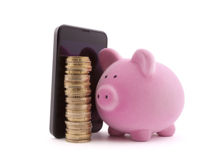 piggy bank: Piggy bank with mobile phone and euro coins. Clipping path included. Stock Photo