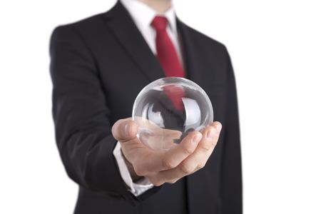 soothsayer: El hombre de negocios que sostiene una bola de cristal aislado en blanco. Aseguramiento camino. Foto de archivo