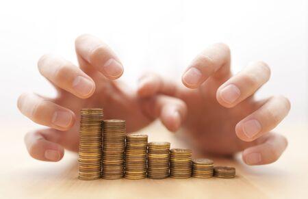 Avidità di denaro. Le mani afferrare le monete. Archivio Fotografico