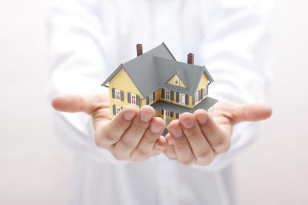 Man holding yellow house miniature Stock Photo