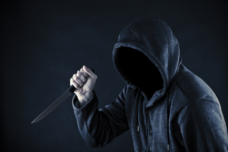 holding a knife: Hooded man with knife in the dark