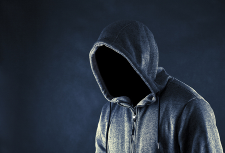 Hooded man in the dark Stock Photo