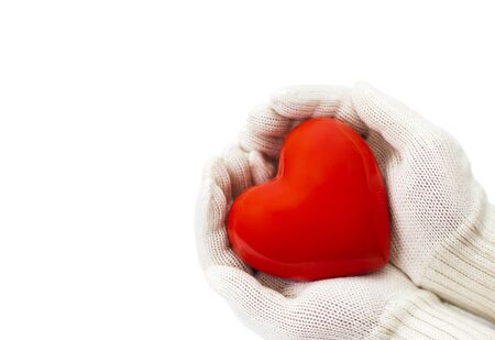 corazon en la mano: Red heart in white warm wool gloves isolated on white with clipping path