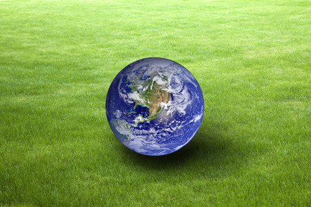 Planet Earth on green grass. Earth Day concept. Earth image provided by Nasa.