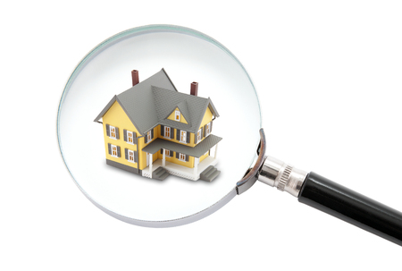 House searching concept with a magnifying glass isolated on white background