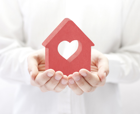 Small house with heart in hands Stockfoto