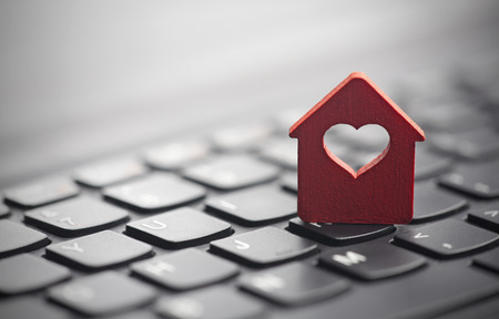 Small red house with heart over laptop keyboard Archivio Fotografico
