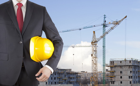 Engineer in black suit holding helmet on construction site Stock Photo