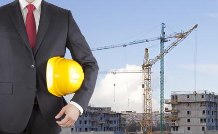 Ingenieur in de zwarte helm van de kostuumholding op bouwwerf Stockfoto - 84467551