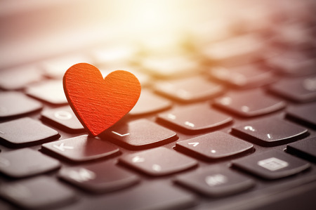 Small red heart on keyboard. Internet dating concept. Standard-Bild