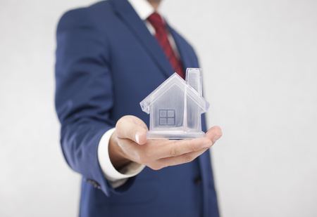 residence: Businessman with crystal house in hand Stock Photo