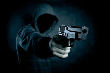 暗闇の中で銃を持つフードの男 写真素材
