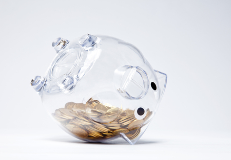 Transparent piggy bank with gold coins upside down