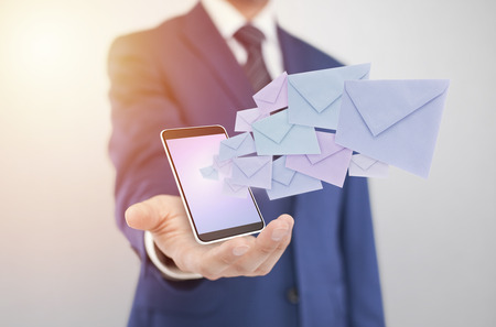 Businessman with smartphone with envelopes coming out of the screen Stockfoto