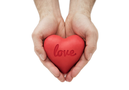 Red heart with imprinted love word in mans hands. Stock Photo