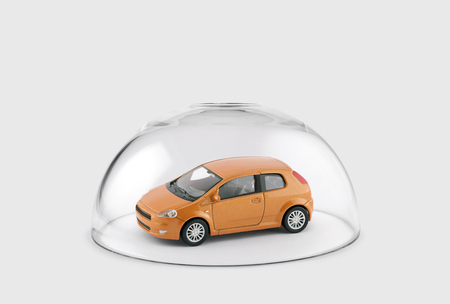 Orange car protected under a glass dome 스톡 콘텐츠