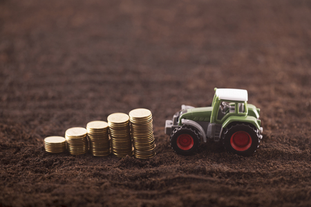 Tractor miniature with coins on fertile soil land Stok Fotoğraf - 102942099