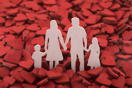 Love and happy family concept. Family figure over hundreds of red hearts. Stock Photo