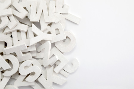 Pile of white painted wooden letters. Typography background composition. Stock Photo