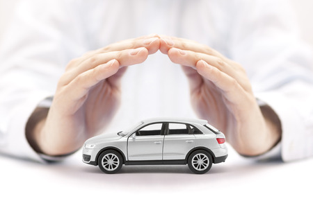 Car insurance. Small silver car covered by hands.
