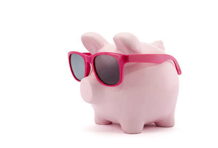 Piggy bank with pink glasses on white background