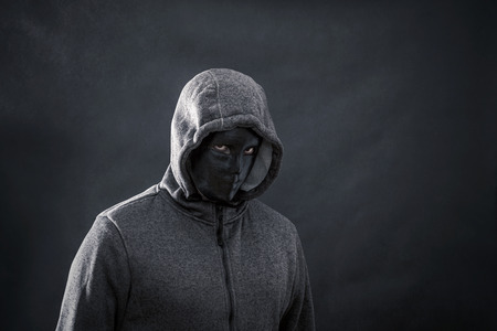 Hooded man with black mask in the dark
