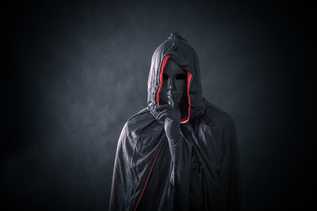 Scary figure with black mask in hooded cloak 스톡 콘텐츠