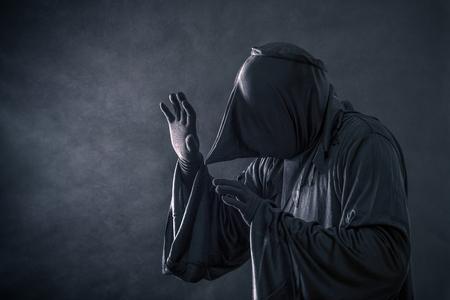 Spooky monster in hooded cloak Imagens