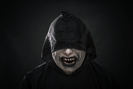 Scary figure in hooded cloak showing his sharp pointy teeth