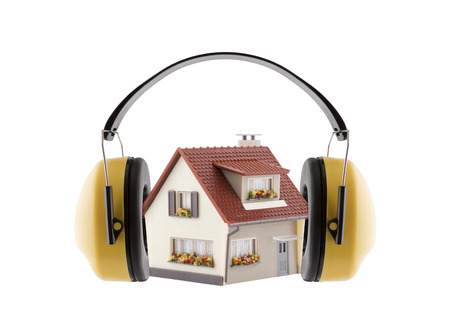 Ochrona przed hałasem. Ochrona słuchu żółte nauszniki z miniaturą domu na białym tle Zdjęcie Seryjne