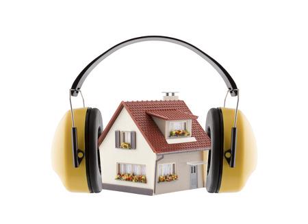 Protección contra el ruido. Protección auditiva orejeras amarillas con casa en miniatura aislado sobre fondo blanco. Foto de archivo