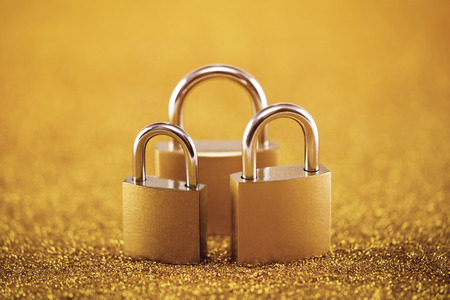 Security concept with three metal padlocks over golden background