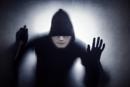 Homme dans un masque avec un couteau derrière un verre rayé poussiéreux