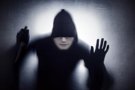 Uomo in maschera con un coltello dietro un vetro graffiato e polveroso